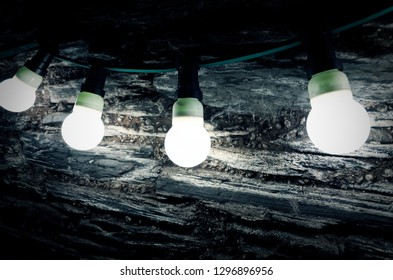 Old tunnel made of slate with energy-saving lamps and light string