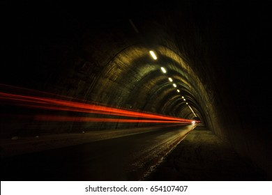 Old tunnel at night with red blurred car lights
