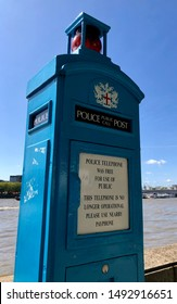 Old turquoise blue London police telephone box by the River Thames in Westminster on a bright sunny day. No longer in use but a reminder of times gone by when we didn't have mobile phones.