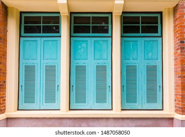 Old turquoise wooden vintage shutter windows with brick wall
