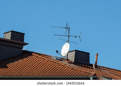 old TV antenna and satellite antenna on the roof