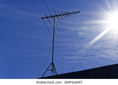 Old TV antenna silhouetted, against a blue sky and low sun.