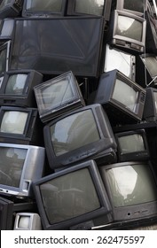 old TV garbage, rubbish, electronic junk, Recycling Electronics, Pile of broken television stacked for disposal. logos, brand names have removed. Great for background, recycle and environmental theme.