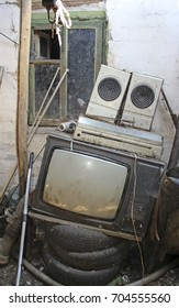 Old TV, music player and speakers against the background of an old house