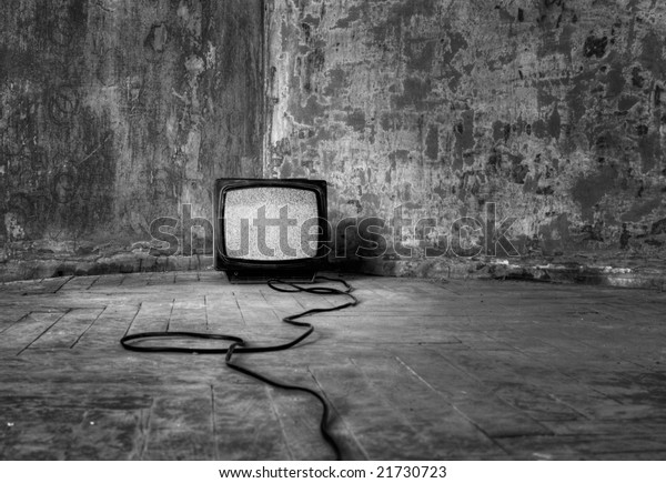 An old TV with the noise on its display standing on the dirty floor