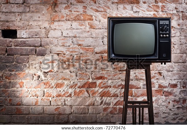 The old TV set against an old brick wall