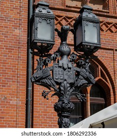 Old two-flame cast iron street lamp with city arms.