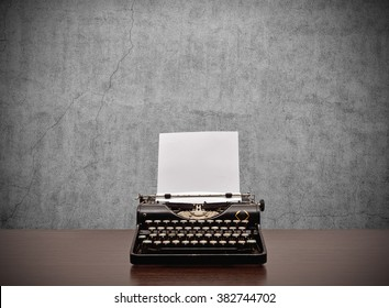 Old typewriter with blank paper on wooden table