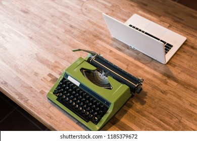 old typewriter and laptop on the table
