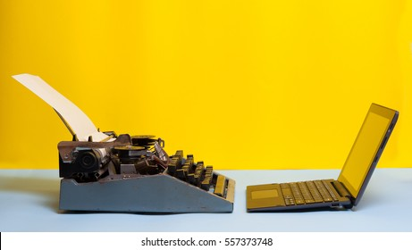 Old typewriter and laptop on table on yellow background. Concept of technology progress. Old vs new; Modern  laptop and an old vintage black typewriter. Space for your text.