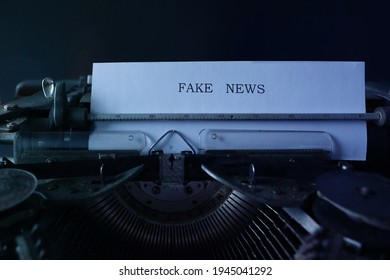 old typewriter on table, words fake news are printed on paper in large size, candle is burning, retro style, concept of information hoax in social media, misleading, exposing deception