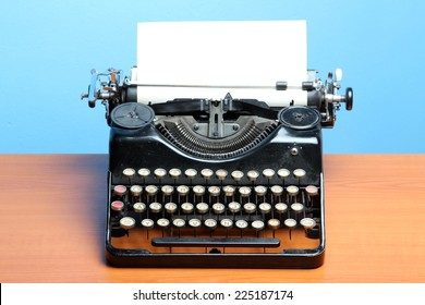 Old typewriter on wood on a blue background