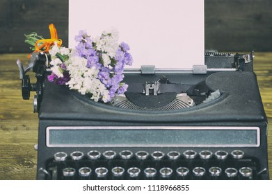 Old typewriter with paper and dried flowers
