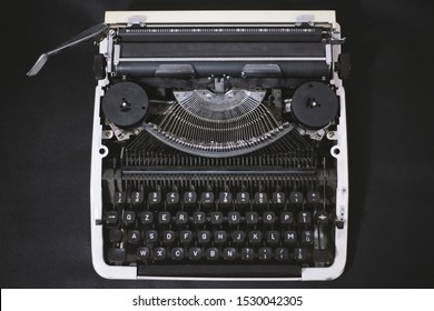 Old Typewriter with QZERTY keyboard on black background. The QZERTY layout was used mostly in Italy, where it was the traditional typewriter layout. Concept: Letterpress printing and inventions