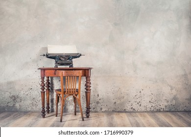 Old typewriter with sheet of paper on retro oak desk and aged chair on wooden floor front grunge concrete wall background. Writer's classic workplace concept in loft room. Vintage style filtered photo