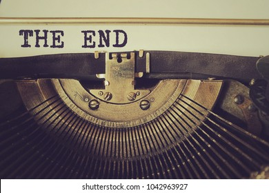"Old typewriter writes text ""The End"" on a piece of paper. Vintage toned photo."