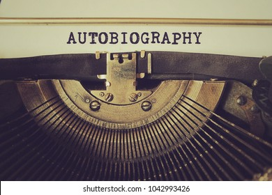 """Old typewriter writes word """"autobiography"""" on a piece of paper. Vintage toned photo."""
