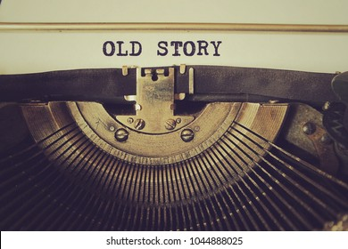 "Old typewriter writes word ""old story"" on a piece of paper. Vintage toned photo."
