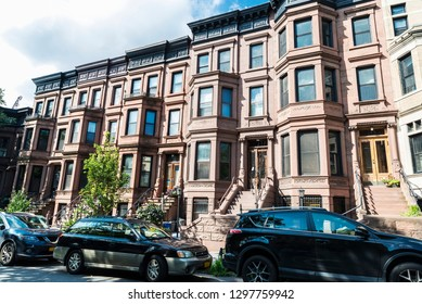 Old typical houses with cars parked in the Brooklyn neighborhood in Manhattan, New York City, USA