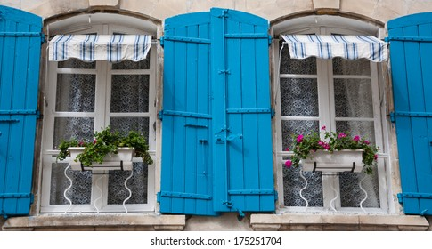 Old typical Mediterranean house with blue wooden shutters and flowers (Arles, Bouches-du-Rhone, Provence-Alpes-Cote d'Azur, France)