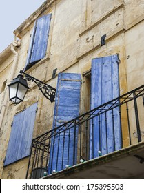 Old typical Mediterranean house with bright blue wooden shutters and stucco wall with peeling paint (Arles, Bouches-du-Rhone, Provence-Alpes-Cote d'Azur, France)