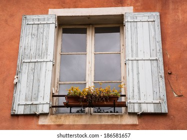 Old typical Mediterranean house with ocher stucco wall, wooden shutters and yellow flowers on the window (Arles, Bouches-du-Rhone, Provence-Alpes-Cote d'Azur, France)