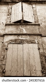 Old typical Mediterranean house with wooden shutters and stucco wall  (Arles, Bouches-du-Rhone, Provence-Alpes-Cote d'Azur, France) Aged photo. Sepia.