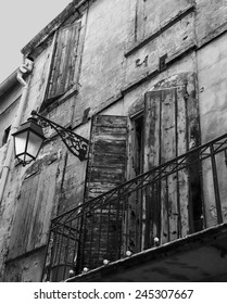 Old typical Mediterranean house with wooden shutters and stucco wall with peeling paint (Arles, Bouches-du-Rhone, Provence-Alpes-Cote d'Azur, France) Aged photo. Black and white.