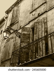 Old typical Mediterranean house with wooden shutters and stucco wall with peeling paint (Arles, Bouches-du-Rhone, Provence-Alpes-Cote d'Azur, France) Aged photo. Sepia.