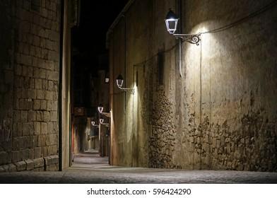 Old typical street by night illuminated by street light. Girona, Catalonia, Spain.