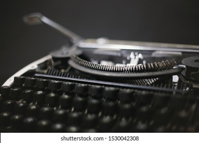 Old Typing Machine with QZERTY, a traditional typewriter keyboard layout used mostly in Italy. Vintage and black background. Concept: Letterpress printing and Movable type. Close up