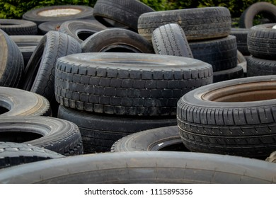 Old tyres dumped in an empty field. Heap Of Old Tires. The end of the road for old tires.