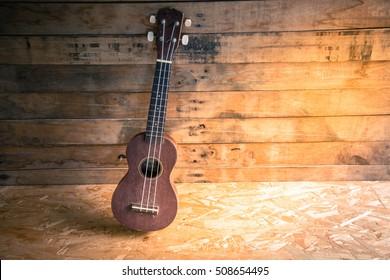 Old ukulele on a wooden background,Still life