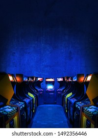 Old Unbranded Vintage Arcade Video Games in a dark gaming room with blue light with glowing displays and concrete wall - vertical photo of retro design with free copy space for a poster or magazine