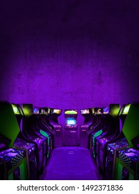 Old Unbranded Vintage Arcade Video Games in a dark gaming room with purple light with glowing displays and concrete wall - vertical photo of retro design with free copy space for a poster or magazine