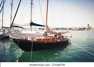 Old uncared wooden boat floating in the sea and docked to port