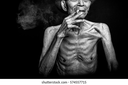 An old uncle who was very thin are smoking cigarettes