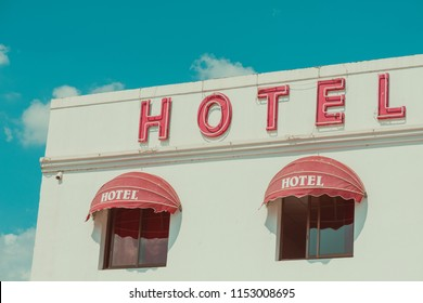 Old unclean hotel facade with vintage neon sign retro color stylized