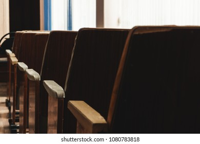 Old and uncomfortable wooden brown seats in a row are installed in a small room for performances in a small school