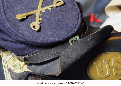 An old uniform cap from the Civil War with Cavalry insignia rests upon a leather ammunition belt with brass emblems.