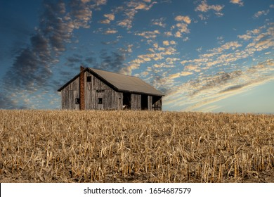 An old, unpainted abandoned wooded building in the middle of a harvested corn field. A brick chimney stands at the end of the building, but the doors and windows are missing.