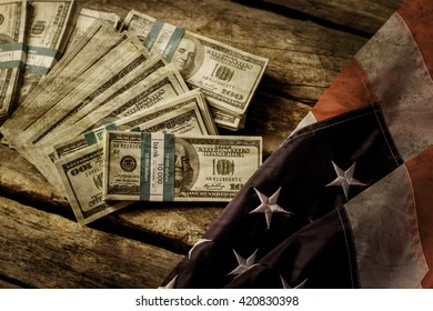 Old USA flag and dollars. Cash laying beside aged flag. Good old times. Nation used to be richer.