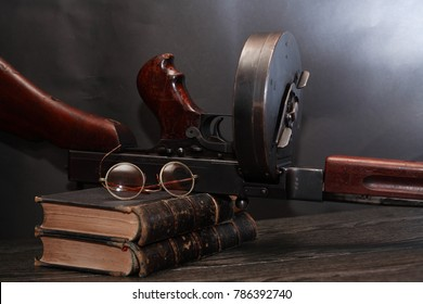 Old USA submachine gun closeup with books and spectacles