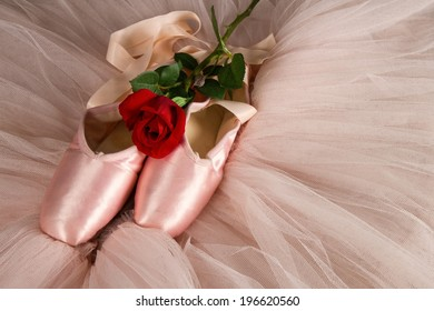Old used ballet slippers lying on floor with rose and pink tutu