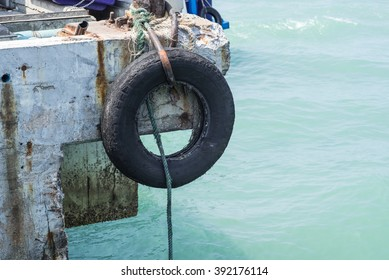 old used car tires as fender on a shipboard