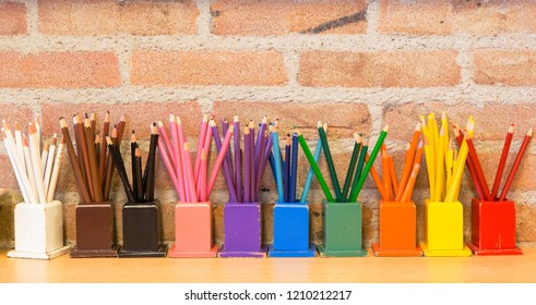 old used color pencils on a row in front of a brick wall off a school