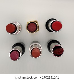lot of old used colorful red shades lipsticks isolated in white background