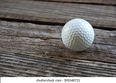 Old used golf ball on wooden background