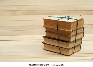 Old and used hardback books or text books on wooden table. Books and reading are essential for self improvement, gaining knowledge and success in our careers, business and personal lives. Copy space.