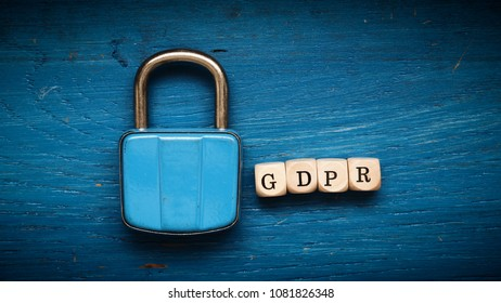 Old used padlock on a blue rustic wooden background, GDPR concept image